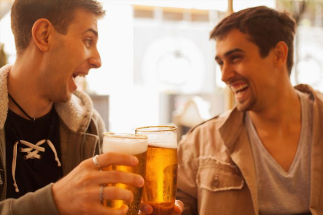 Two young men laughing and toasting with beer